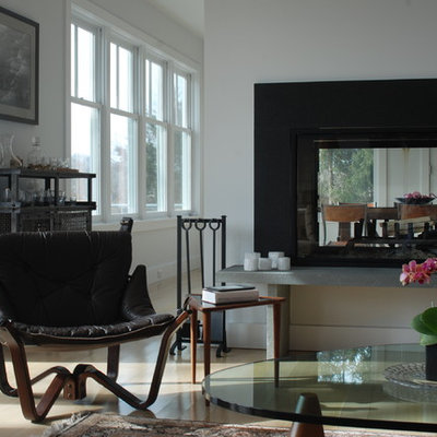 Trendy living room photo in New York with a two-sided fireplace and white walls