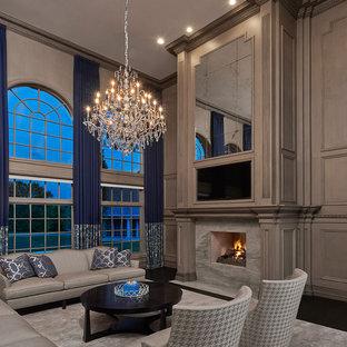 デトロイトの巨大なトラディショナルスタイルのおしゃれなLDK (フォーマル、グレーの壁、濃色無垢フローリング、埋込式メディアウォール、両方向型暖炉、石材の暖炉まわり) の写真