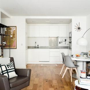 Inspiration för små nordiska allrum med öppen planlösning, med ett bibliotek, vita väggar, laminatgolv och en fristående TV