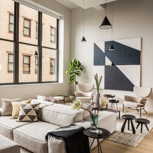 Ejemplo de salón para visitas tipo loft, contemporáneo, de tamaño medio, sin chimenea y televisor, con paredes grises, suelo de madera clara y suelo beige