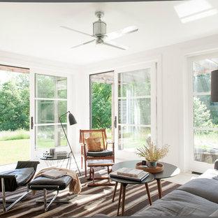Esempio di un soggiorno moderno di medie dimensioni e aperto con pareti bianche, pavimento in legno verniciato, camino bifacciale, cornice del camino in pietra e nessuna TV