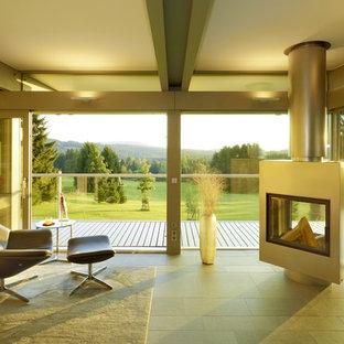 Foto di un grande soggiorno minimalista aperto con pareti grigie, pavimento con piastrelle in ceramica, camino bifacciale e cornice del camino in metallo