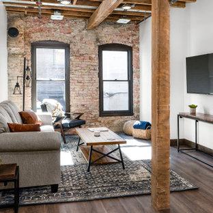 Inspiration för mellanstora industriella allrum med öppen planlösning, med ljust trägolv, en väggmonterad TV, brunt golv och vita väggar