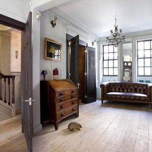 Inredning av ett eklektiskt separat vardagsrum, med vita väggar, ett finrum, en standard öppen spis, en spiselkrans i sten och ljust trägolv