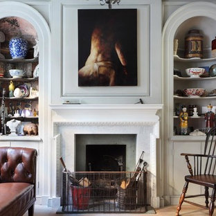 ロンドンのエクレクティックスタイルのおしゃれなリビング (ライブラリー、グレーの壁、標準型暖炉、淡色無垢フローリング、コンクリートの暖炉まわり) の写真