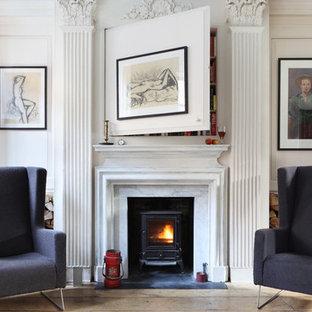 ロンドンのヴィクトリアン調のおしゃれなリビング (ライブラリー、白い壁、淡色無垢フローリング、薪ストーブ) の写真