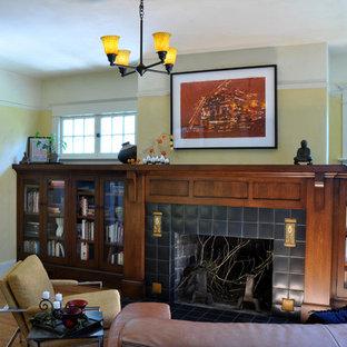 Foto di un soggiorno american style di medie dimensioni e aperto con libreria, pareti gialle, pavimento in legno massello medio, camino classico e cornice del camino piastrellata