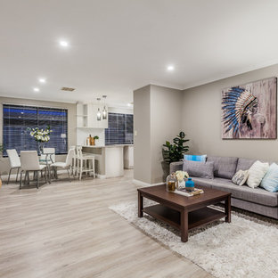 This is an example of a transitional open concept living room in Perth with grey walls and light hardwood floors.