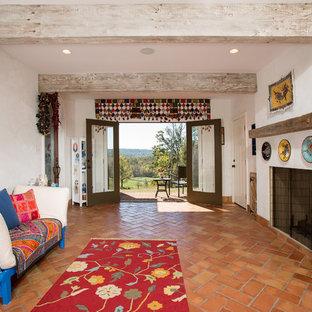 Стильный дизайн: гостиная комната с полом из терракотовой плитки, оранжевым полом и стандартным камином - последний тренд