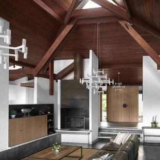 Immagine di un grande soggiorno moderno aperto con sala formale, pareti bianche, pavimento in ardesia, camino ad angolo, cornice del camino in intonaco, TV nascosta e pavimento grigio