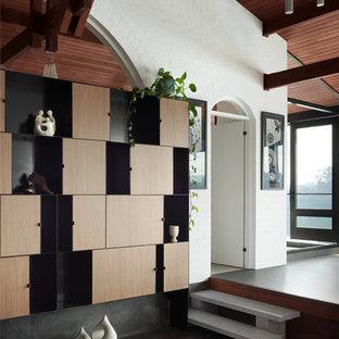 Modelo de salón para visitas abierto, retro, grande, con paredes blancas, suelo de pizarra, chimenea de esquina, marco de chimenea de yeso, televisor retractable y suelo gris