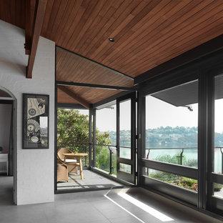 Großes, Repräsentatives, Offenes Retro Wohnzimmer mit weißer Wandfarbe, Schieferboden, Eckkamin, verputzter Kaminumrandung, verstecktem TV und grauem Boden in Sydney