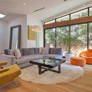 ロサンゼルスの中サイズのミッドセンチュリースタイルのおしゃれな独立型リビング (白い壁、無垢フローリング、横長型暖炉、石材の暖炉まわり、テレビなし、黄色い床) の写真