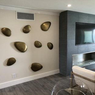 マイアミの小さいビーチスタイルのおしゃれなLDK (白い壁、クッションフロア、標準型暖炉、タイルの暖炉まわり、埋込式メディアウォール、グレーの床) の写真