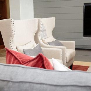 Diseño de salón abierto, moderno, grande, con paredes grises, suelo de piedra caliza, chimenea lineal, marco de chimenea de piedra y pared multimedia