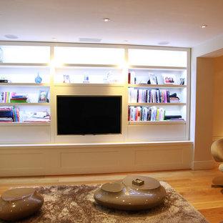 Foto di un piccolo soggiorno moderno chiuso con libreria, pareti bianche, parquet chiaro, nessun camino e parete attrezzata