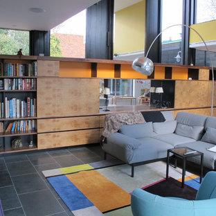 Idee per un piccolo soggiorno minimalista aperto con libreria, pareti bianche, pavimento in ardesia, nessun camino e nessuna TV