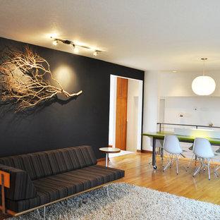 Example of a midcentury modern loft-style medium tone wood floor living room design in Portland with black walls