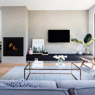 Photo of a contemporary open concept living room in Melbourne with grey walls, medium hardwood floors, a standard fireplace, a wall-mounted tv and brown floor.