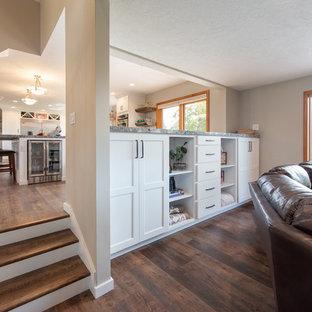 Imagen de salón para visitas abierto, actual, con paredes grises, suelo de madera en tonos medios, chimenea tradicional, pared multimedia y suelo marrón