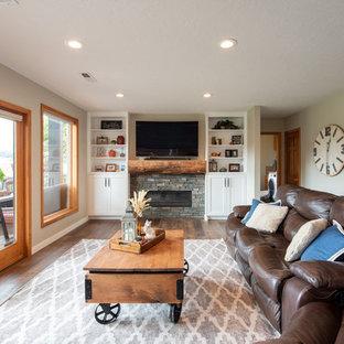 Aménagement d'un salon contemporain ouvert avec une salle de réception, un mur gris, un sol en bois brun, une cheminée standard, un manteau de cheminée en pierre de parement, un téléviseur encastré et un sol marron.