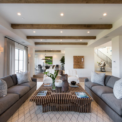 Example of a huge transitional open concept light wood floor living room design in Orange County with a bar, white walls, a standard fireplace, a concrete fireplace and no tv
