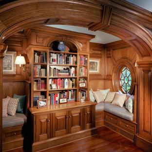 Foto de biblioteca en casa cerrada, tradicional, pequeña, sin chimenea y televisor, con paredes marrones, suelo de madera en tonos medios y suelo marrón