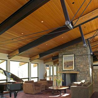 Modelo de salón abierto, contemporáneo, grande, con paredes blancas, suelo de cemento, estufa de leña, marco de chimenea de piedra y suelo marrón