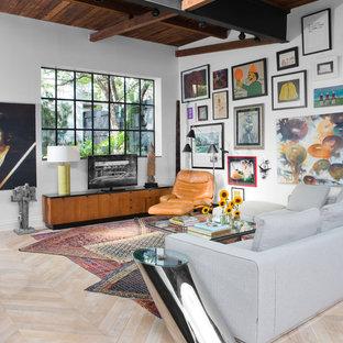 Idéer för ett mellanstort industriellt allrum med öppen planlösning, med vita väggar, en fristående TV, ljust trägolv och beiget golv