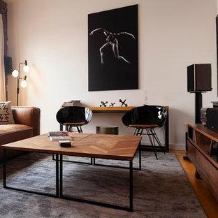 Ejemplo de salón industrial, de tamaño medio, con paredes blancas, suelo de madera en tonos medios, televisor colgado en la pared y suelo marrón