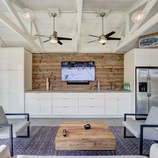 オクラホマシティの大きいビーチスタイルのおしゃれな独立型リビング (白い壁、コンクリートの床、暖炉なし、壁掛け型テレビ) の写真