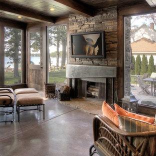 デトロイトの広いインダストリアルスタイルのおしゃれなLDK (フォーマル、ベージュの壁、コンクリートの床、標準型暖炉、石材の暖炉まわり、壁掛け型テレビ) の写真