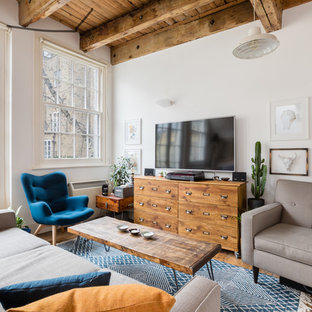 Industrial open plan living room in London with white walls, medium hardwood flooring, a wall mounted tv and brown floors.
