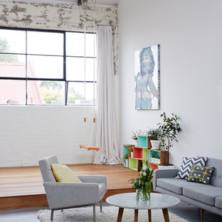 Urban formal concrete floor living room photo in Melbourne with white walls