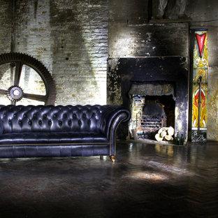 ロンドンの中サイズのインダストリアルスタイルのおしゃれな独立型リビング (無垢フローリング、標準型暖炉、コンクリートの暖炉まわり) の写真