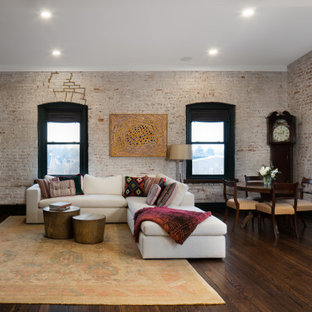 Inspiration for an expansive contemporary open concept living room in Other with multi-coloured walls, medium hardwood floors, a concrete fireplace surround, a wall-mounted tv, brown floor and brick walls.