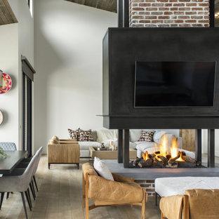 Idées déco pour un salon industriel ouvert avec un bar de salon, un mur blanc, un sol en bois clair, une cheminée double-face, un manteau de cheminée en brique, un téléviseur fixé au mur, un sol marron, un plafond voûté et un mur en parement de brique.