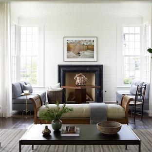 ヒューストンの広いトラディショナルスタイルのおしゃれなLDK (白い壁、無垢フローリング、標準型暖炉、石材の暖炉まわり、茶色い床) の写真