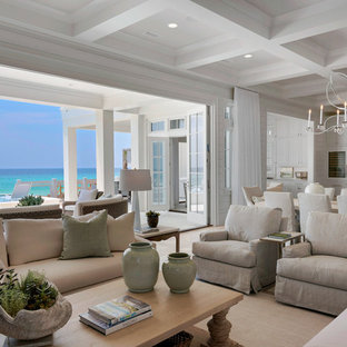 Inspiration for a huge beach style open concept travertine floor living room remodel in Miami with white walls, a standard fireplace, a tile fireplace and a wall-mounted tv