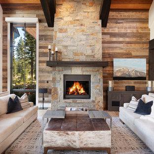他の地域の大きいラスティックスタイルのおしゃれなLDK (白い壁、無垢フローリング、石材の暖炉まわり、茶色い床、壁掛け型テレビ、標準型暖炉) の写真