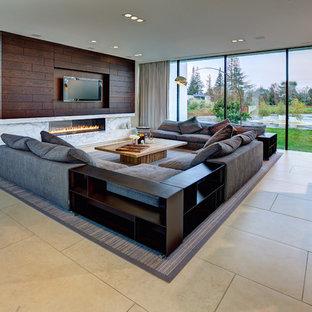 Modelo de salón para visitas abierto, minimalista, grande, con chimenea lineal, televisor colgado en la pared, paredes blancas, suelo de piedra caliza y marco de chimenea de piedra