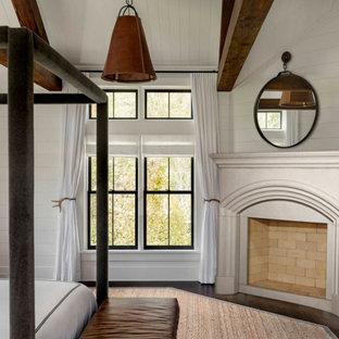 Réalisation d'un petit salon champêtre avec un mur gris, un sol en bois brun, une cheminée standard, un manteau de cheminée en pierre, un sol marron, un plafond en poutres apparentes et du lambris de bois.