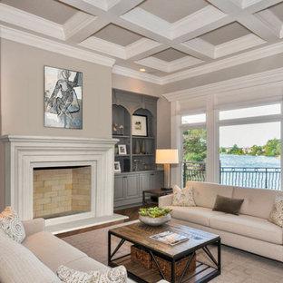 Exemple d'un salon bord de mer de taille moyenne avec un mur gris, une cheminée standard, un manteau de cheminée en pierre et un plafond à caissons.