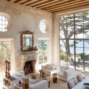 Ejemplo de salón para visitas abierto, mediterráneo, grande, sin televisor, con paredes beige, suelo de piedra caliza, chimenea tradicional y marco de chimenea de piedra