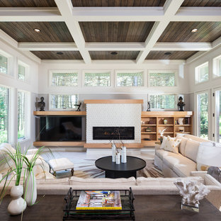This is an example of a classic enclosed living room in Other with white walls, a ribbon fireplace, a stone fireplace surround, a wall mounted tv and beige floors.