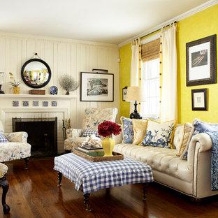 Esempio di un soggiorno chic di medie dimensioni e aperto con pareti gialle, parquet scuro, camino classico, cornice del camino in mattoni e nessuna TV