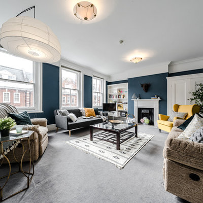 Example of a transitional carpeted living room design in London with blue walls and a standard fireplace
