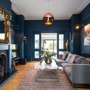 Ispirazione per un soggiorno bohémian di medie dimensioni e chiuso con pareti blu, parquet chiaro, camino classico, cornice del camino in metallo, TV autoportante, pavimento beige e sala formale