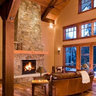 デンバーの大きいラスティックスタイルのおしゃれなLDK (標準型暖炉、木材の暖炉まわり、ベージュの壁、無垢フローリング、据え置き型テレビ、フォーマル、茶色い床) の写真
