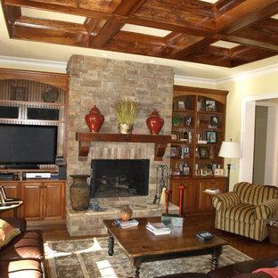 Diseño de salón abierto, clásico, de tamaño medio, con paredes amarillas, suelo de madera en tonos medios, chimenea tradicional, marco de chimenea de piedra y pared multimedia